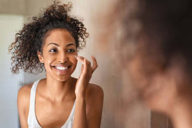 ragazza massaggiando il viso di fronte a uno specchio